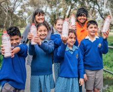 Antonine College student Kavi and Mayor with bottles